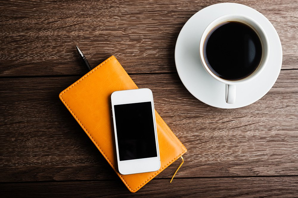 organizer with cup of coffee and mobile phone on desk